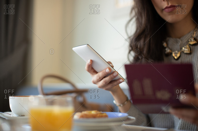 Cropped shot of young woman with digital tablet electronically checking in while having breakfast at boutique hotel in Italy