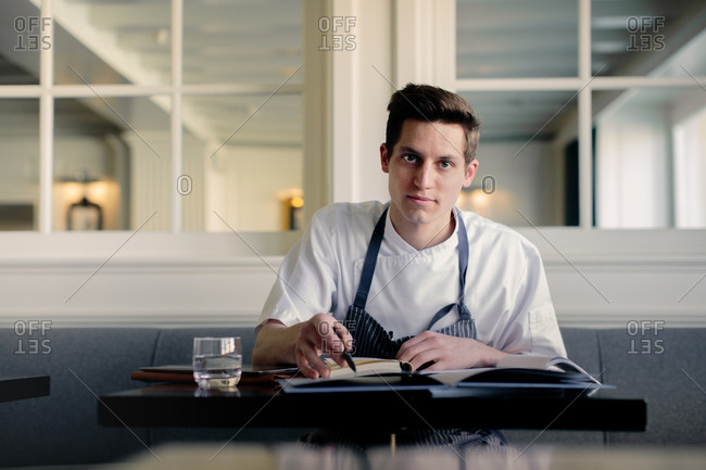 Young male chef doing paperwork and talking on smartphone in restaurant
