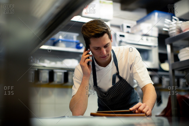 Young male chef reading digital tablet and talking on smartphone in kitchen