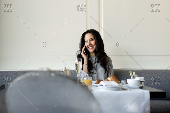 Young woman talking on smartphone while having champagne breakfast at boutique hotel in Italy