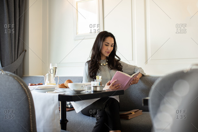 Young woman reading book while having champagne breakfast at boutique hotel in Italy