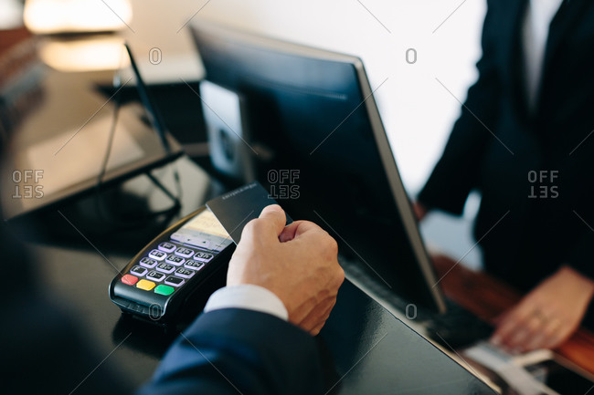 Businessman making contactless payment at hotel reception