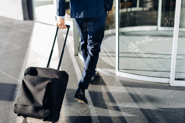 Businessman with wheeled luggage entering revolving doors of building