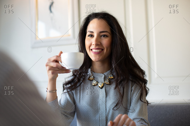 Young woman drinking coffee inboutique hotel in Italy