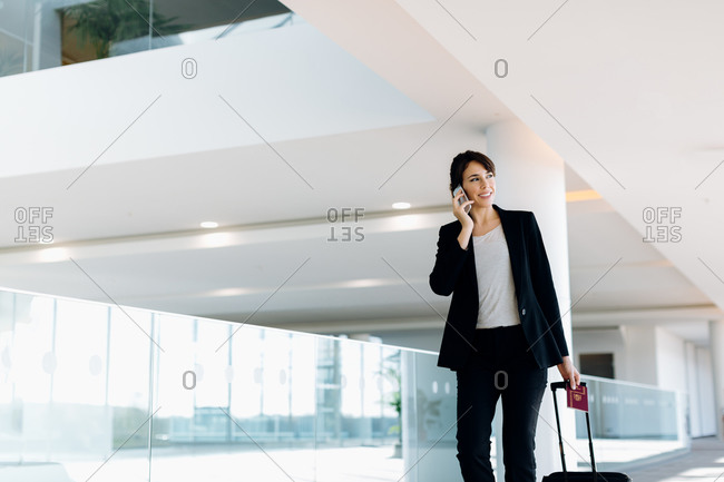 Businesswoman with wheeled luggage in hotel building