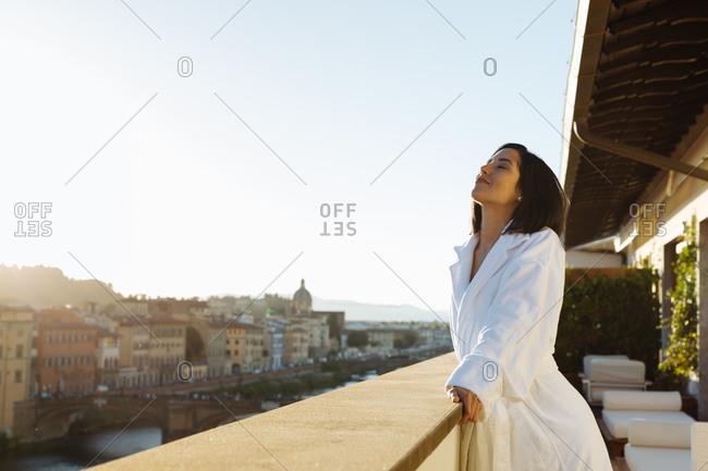 Woman enjoying sun on hotel balcony, Florence, Toscana, Italy
