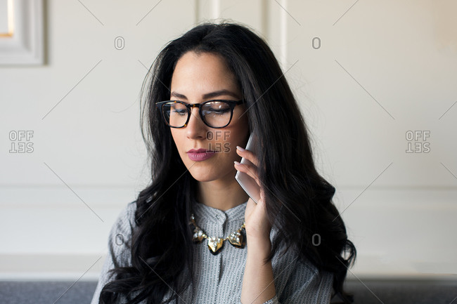 Young woman talking on smartphone inboutique hotel in Italy