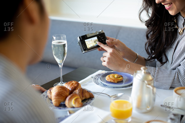Young woman pointing at digital camera while having champagne breakfast at boutique hotel in Italy