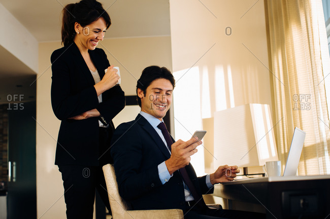 Businessman and businesswoman sharing text message in hotel room