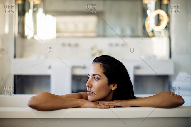 Woman relaxing in bathtub in suite