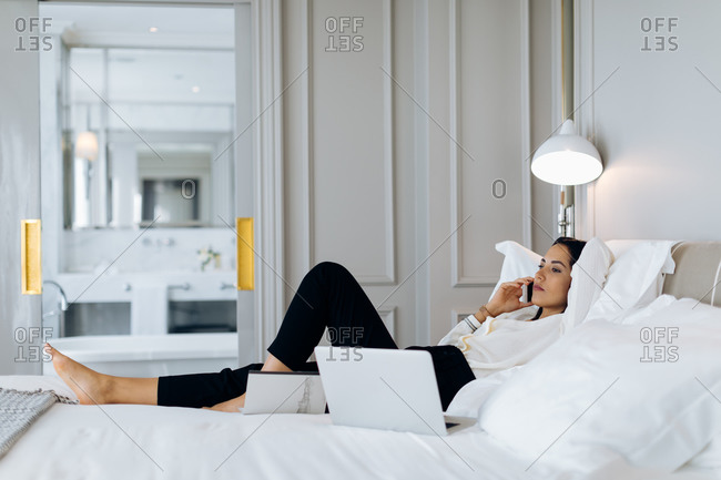 Businesswoman using smartphone and laptop in suite