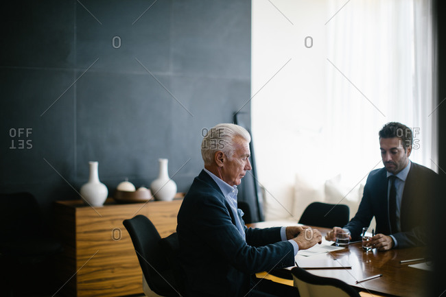 Two businessmen meeting at boardroom table