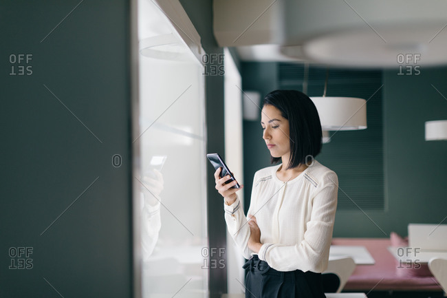 Young businesswoman in hotel looking at smartphone