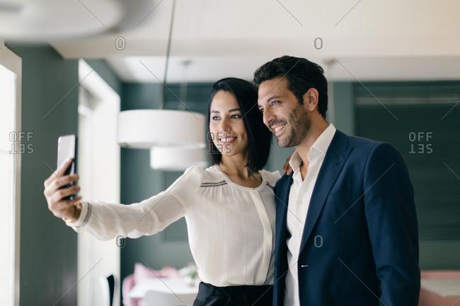 Couple in hotel taking smartphone selfie