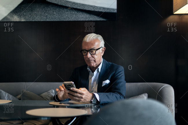 Senior businessman sitting in hotel table using smartphone touchscreen