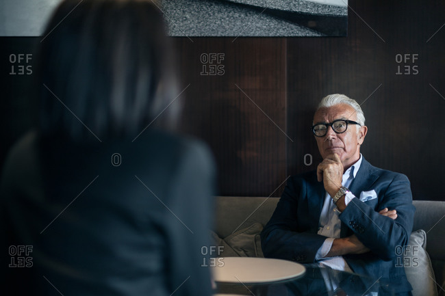 Senior businessman sitting in hotel table meeting with businesswoman, over shoulder view