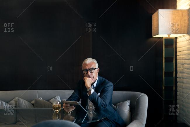 Senior businessman sitting in hotel table using digital tablet, portrait