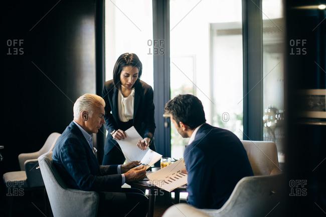 Businesswoman and men having meeting in hotel restaurant