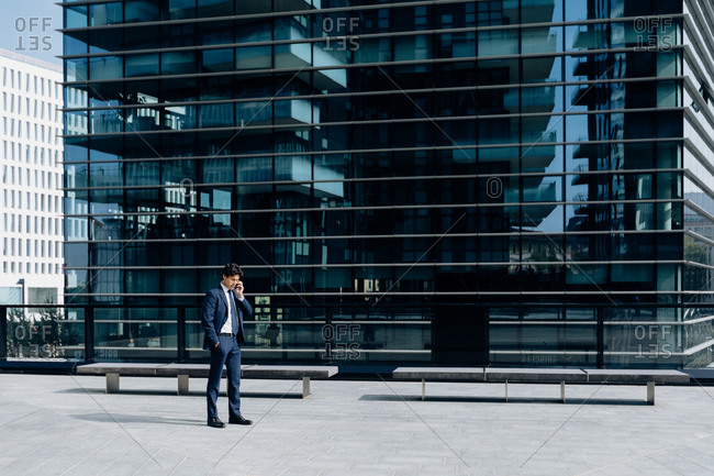 Businessman using smartphone in front of office building