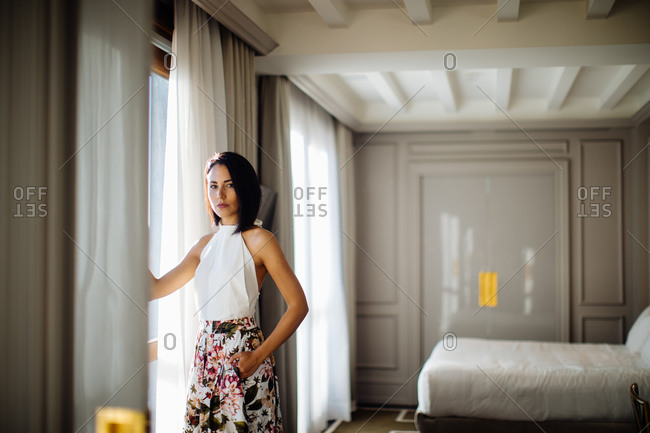 Fashionable woman beside window in suite