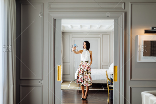 Fashionable woman taking selfie in suite
