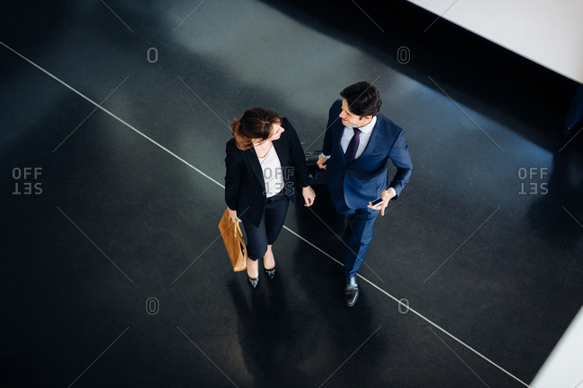 Businessman and businesswoman with wheeled luggage in hotel building