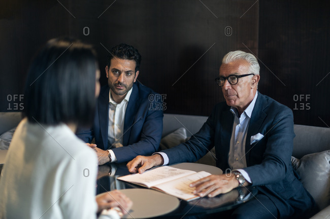 Two businessmen sitting in hotel table meeting with businesswoman