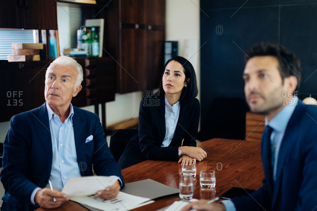 Businessmen and woman watching presentation from boardroom table