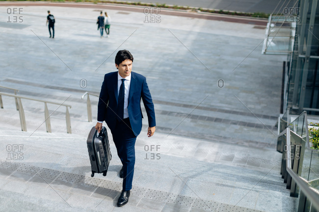 Businessman walking up stairway with carry on suitcase