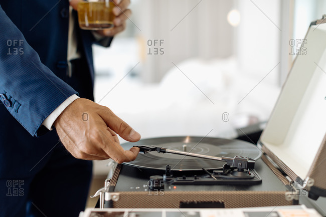 Businessman with iced drink, playing turntable in suite
