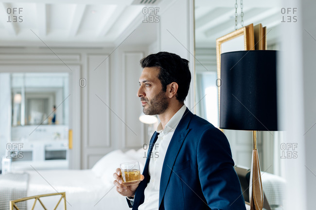 Businessman with iced drink, deep in thoughts in suite