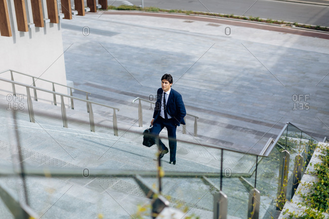 Businessman walking up stairway with a bag