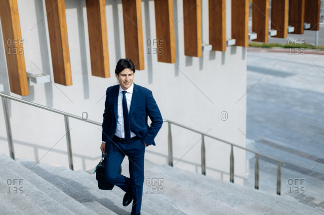 Businessman walking up stairway, carrying a bag