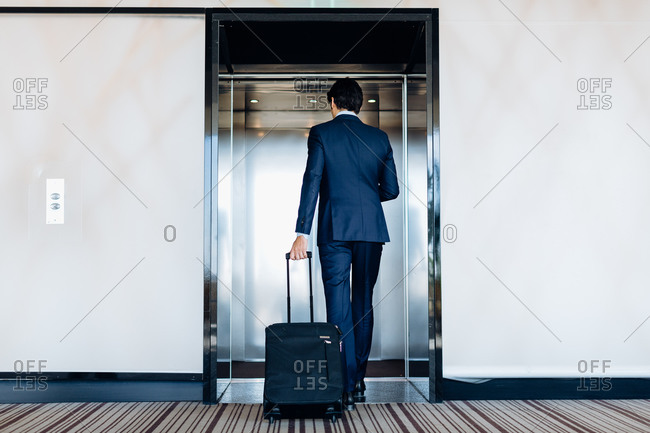 Businessman with wheeled luggage entering hotel lift