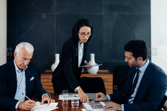 Businessmen and woman looking at charts and paperwork at boardroom table