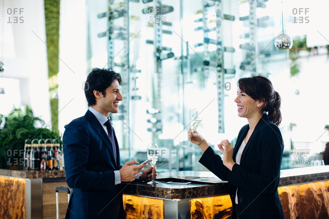 Businessman and businesswoman having drink at bar