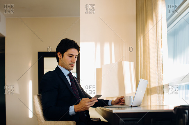 Businessman texting while using laptop by hotel room window