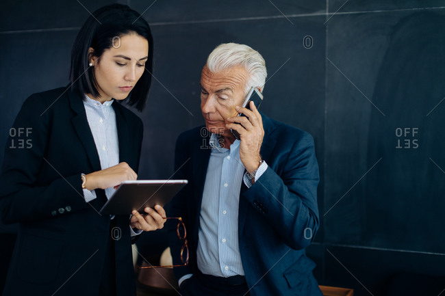 Businessman and woman looking at digital tablet and making smartphone call in boardroom
