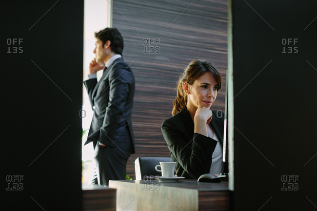 Businessman and businesswoman working in hotel bedroom