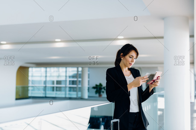 Businesswoman using mobile phone for electronic check-in