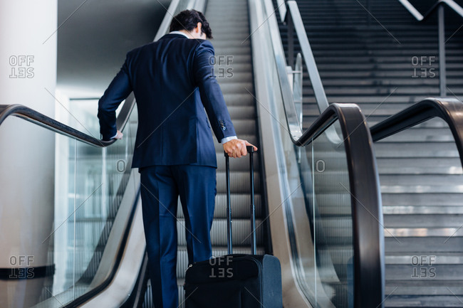 Businessman with wheeled luggage on hotel escalator