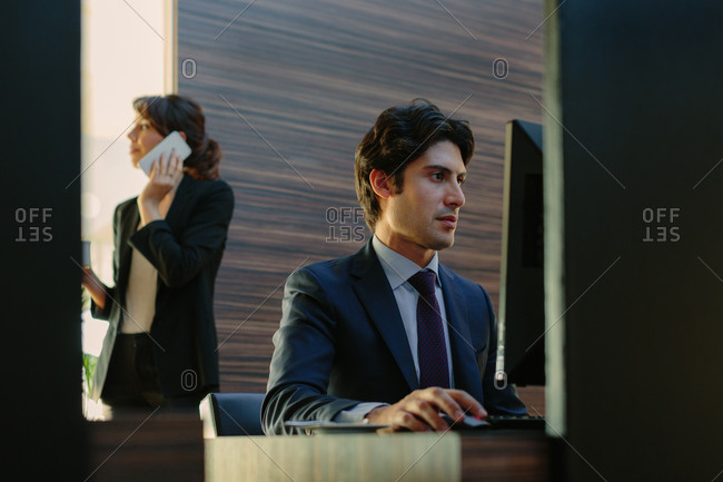 Businessman and businesswoman working in business center in hotel