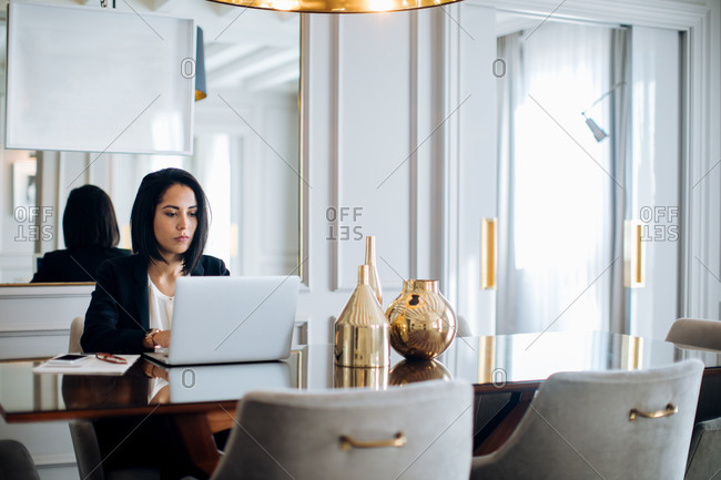 Businesswoman using laptop in suite