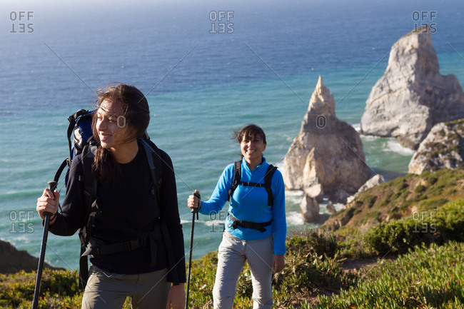 Two women with rucksacks and hiking poles walking along the coastline overlooking sea stacks.