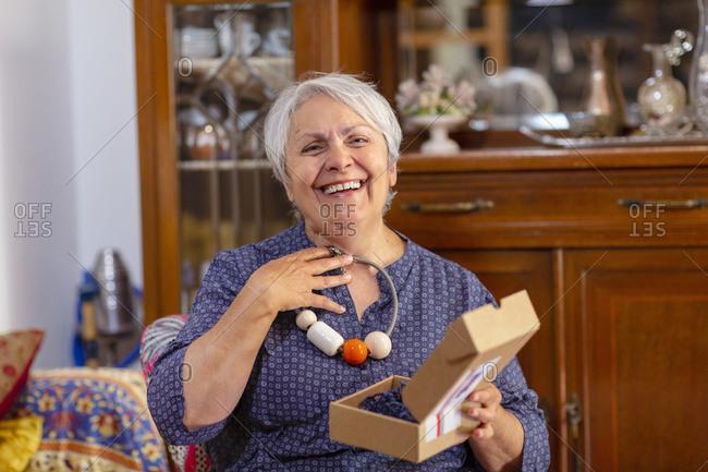 Senior woman holding birthday present, online celebration with her family during Coronavirus lockdown.