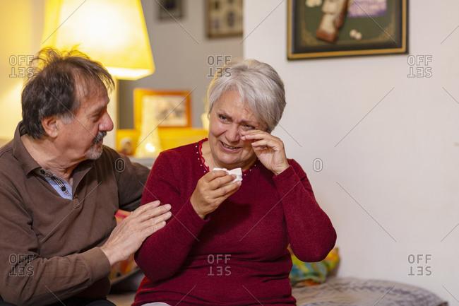Senior man consoling his crying wife during Coronavirus lockdown.