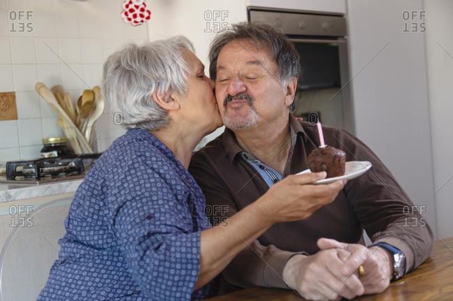 Senior man and woman holding birthday cake, kissing, online celebration during Coronavirus lockdown.