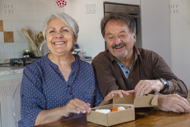 Senior man and woman holding birthday present, online celebration during Coronavirus lockdown.