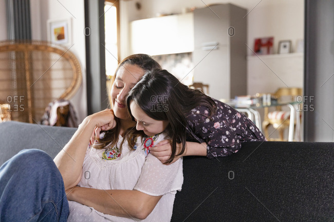Daughter hugging her mother sitting on living room sofa, during Coronavirus lockdown.
