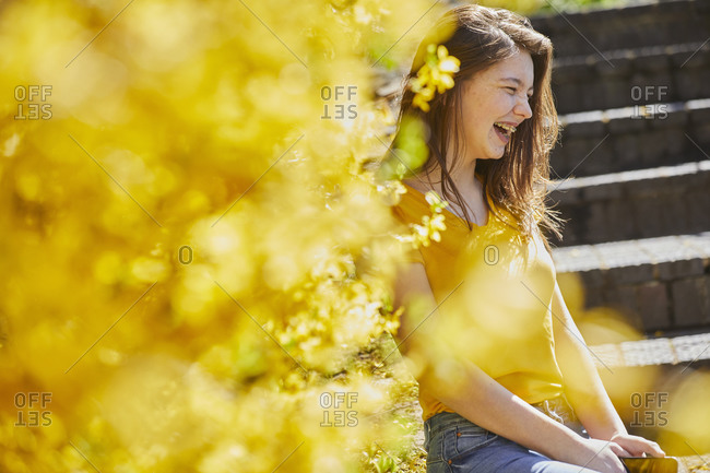 Teenage girl sitting outdoors on steps, yellow Forsythia in foreground.